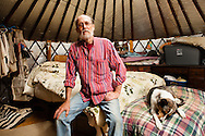 "James Massey poses in his 20-foot bedroom yurt, one of two yurts he built, added rooms onto, and now shares with his wife in Albany, Ohio, on Oct. 18, 2011. Massey, who has set up his yurts in five states since the early 1980s but has kept his yurts in Albany for several years, says, ""I lived in tipis for a while and they're fine, but you've got to stay there with a tipi. With one of these, you can kind of go off and leave it, in a way. So it's not quite so restrictive of staying there."""