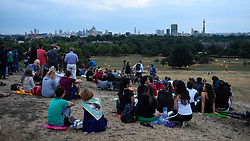 "© Licensed to London News Pictures. 27/07/2018. LONDON, UK.  Large numbers of people gather on Primrose Hill to witness the lunar eclipse, known as a ""Blood Moon"", over the capital.  Unfortunately, low cloud prevented them seeing this century's longest lunar eclipse.  Photo credit: Stephen Chung/LNP"