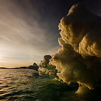 Norway, Svalbard, Langøya Island, Setting sun lights glacial iceberg on summer evening