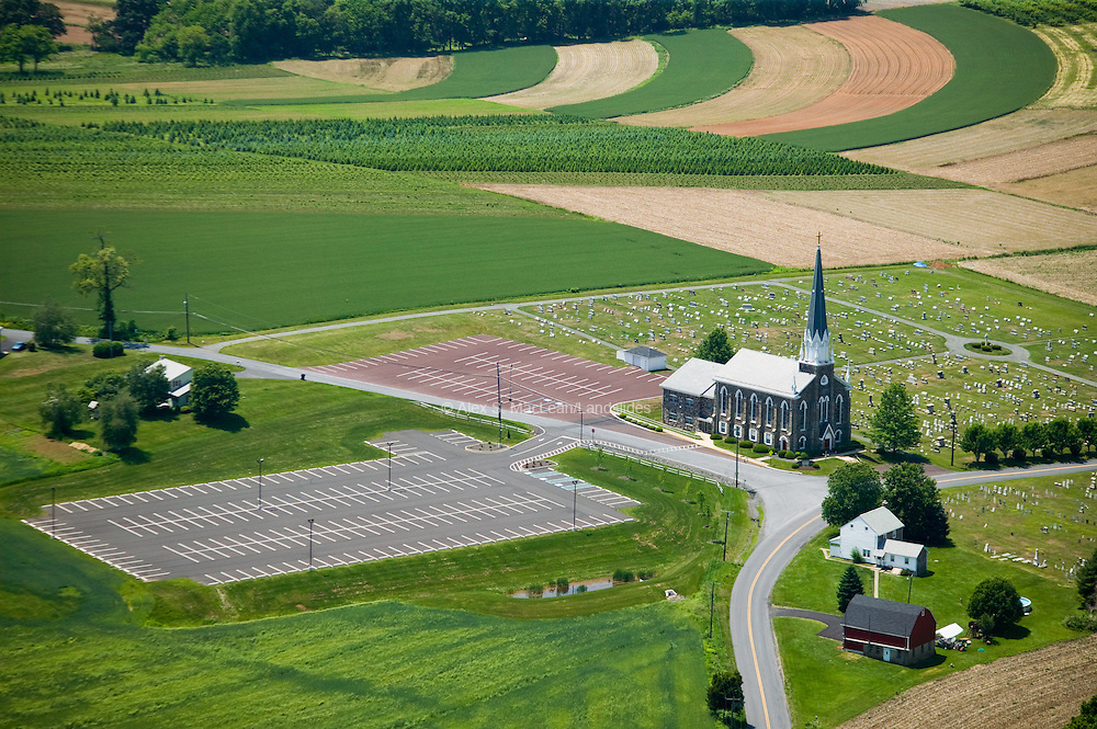 Parking lots at this small rural church are larger than the building itself, which has a seating capacity of more than 330. Juxtaposing the containments, the church and parking lots, illustrates the amount of space that cars require in relation to their drivers.  Today the church's congregation, which was once primarily local German farmers, commutes from increasingly long distances.