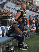 Aug 25, 2017; Seattle, WA, USA; Seattle Seahawks defensive end Michael Bennett (72) sits on the bench with center Justin Britt (68) standing by his side during the playing of the national anthem before a NFL football game against the Kansas City Chiefs at CenturyLink Field.