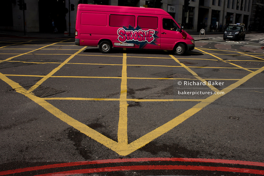 Bright pink delivery van turns mid-way over a yellow box junction grid in a City of London street.