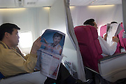 Passengers reading newspapers in a Korean Air Boeing 737-800 flying from Jeju island to Kwangju.