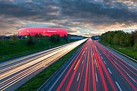 Die Allianz Arena im Münchner Norden in Rot beleuchtet bei Nacht und die Autobahn A9 mit Lichtspuren.