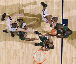 Virginia Cavaliers guard J.R. Reynolds (2) shoots over Miami Hurricanes forward Dwayne Collins (21) and Miami Hurricanes guard Anthony Harris (12).  The University of Virginia Cavaliers defeated the Miami Hurricanes Men's Basketball Team 81-70 at the John Paul Jones Arena in Charlottesville, VA on February 3, 2007.