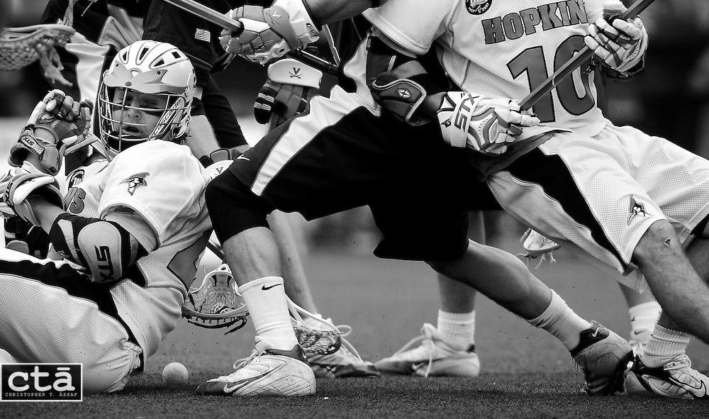 The ball, and his stick, got away from Johns Hopkins attacker Kevin Huntley (24) and he quickly finds himself surrounded as players scramble for the loose ball late in the fourth quarter. Johns Hopkins lost 7-5 to Virginia at Homewood Field.