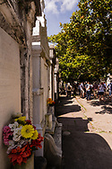 New Orleans, LA, USA -- May 26, 2019.  Vertical photo of tourists visiting St Louis Cemetery #3 in the garden district of New Orleans.