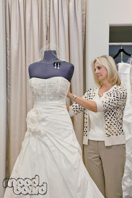 Senior female owner adjusting wedding dress on mannequin in bridal store