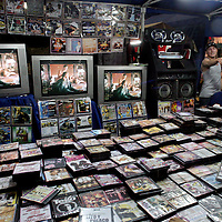"Buhoneros - Young men sell bootleg movies and music in the Sabana Grande neighborhood of Caracas Friday, December 15, 2006.  Buhoneros, thousands of workers who sell products from clothing and accessories to household goods and bootleg DVDs make up the controversial ""informal economy.""  While many Caracas residents complain that the buhoneros have taken over streets with their makeshift marketplace, many buhoneros give thanks to Venezuelan President Hugo Chavez for allowing them a way to survive by creating their own small businesses."