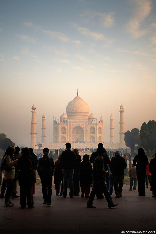 A crowd of tourists enter the front gateway revealing a full view of the Taj Mahal at sunrise.