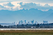 The tidal wetlands at Blackie Spit in Surrey, British Columbia, Canada. Buildings in background are the Metrotown area of Burnaby, BC, and the mountains behind are the North Shore Mountains (including The Lions).