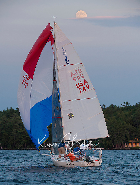 """Winnipesaukee Yacht Club J80 """"Dolce"""" sailboat finishes the race under the rising Blue Moon on Thursday evening.  (Karen Bobotas/for the Laconia Daily Sun)"""