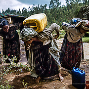 The water from the river that 25 year old Tesomech (in the middle) goes to is also not safe. In order to supply her eight member family with water, Tesomech must carry a 35 litre container twice a day for four hours. She suffers from frequent backaches. Gurage, Ethiopia.