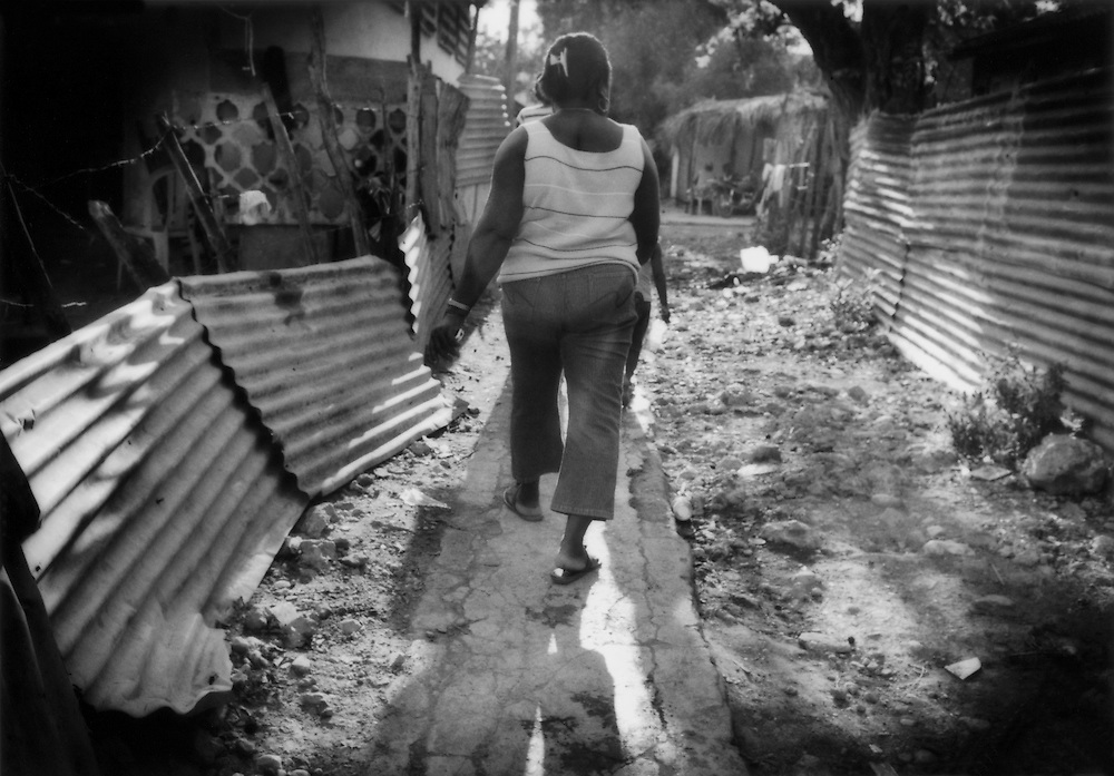 Haitian woman walks through trash-strewn Villa Central Batey at the end of the day, Barahona, Dominican Republic.