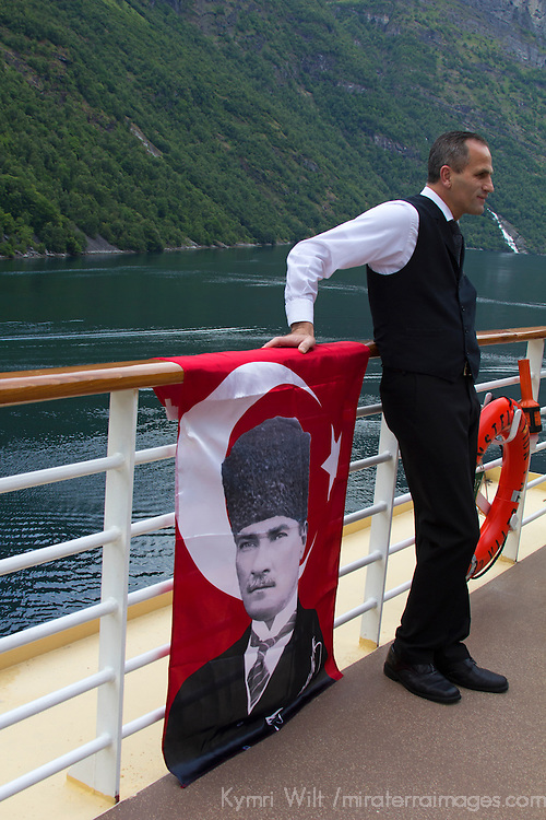 Europe, Norway, Geiranger. A Turkish crewmember poses with Ataturk on a cruiseship in Norway.
