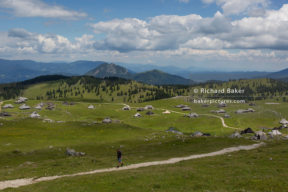 Walkers away from the collection of Slovenian herders' mountain huts in Velika Planina, on 26th June 2018, in Velika Planina, near Kamnik, Slovenia. Velika Planina is a mountain plateau in the Kamnik–Savinja Alps - a 5.8 square kilometres area 1,500 metres (4,900 feet) above sea level. Otherwise known as The Big Pasture Plateau, Velika Planina is a winter skiing destination and hiking route in summer. The herders' huts became popular in the early 1930s as holiday cabins (known as bajtarstvo) but these were were destroyed by the Germans during WW2 and rebuilt right afterwards by Vlasto Kopac in the summer of 1945.