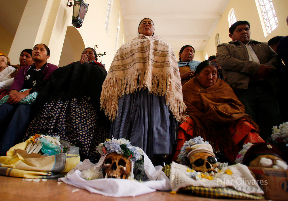 Bolivians pray in front of skulls in a church during the Day of Skulls at the General Cemetery in La Paz November 8, 2009. Bolivians who keep close relatives' skulls at home as a macabre talisman flock to the cemetery chapel once a year to have the craniums blessed and to bring themselves good luck in the future.