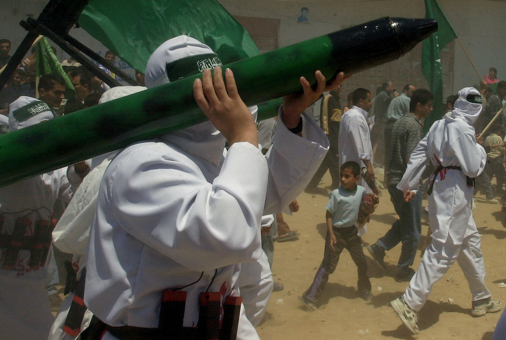 A Palestinian child runs amongst Hamas demonstrators dressed as suicide bombers with fake dynamite wrapped around their waste holding models of mortars during a  rally in the refugee camp of Jabalia in the Gaza Strip Friday April 27, 2001.