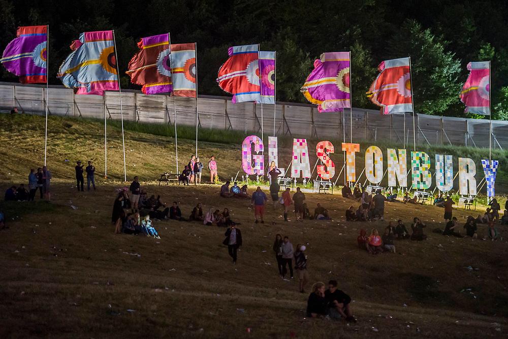 Early friday morning people sit below the Glastonbury sign - The 2017 Glastonbury Festival, Worthy Farm. Glastonbury, 23 June 2017
