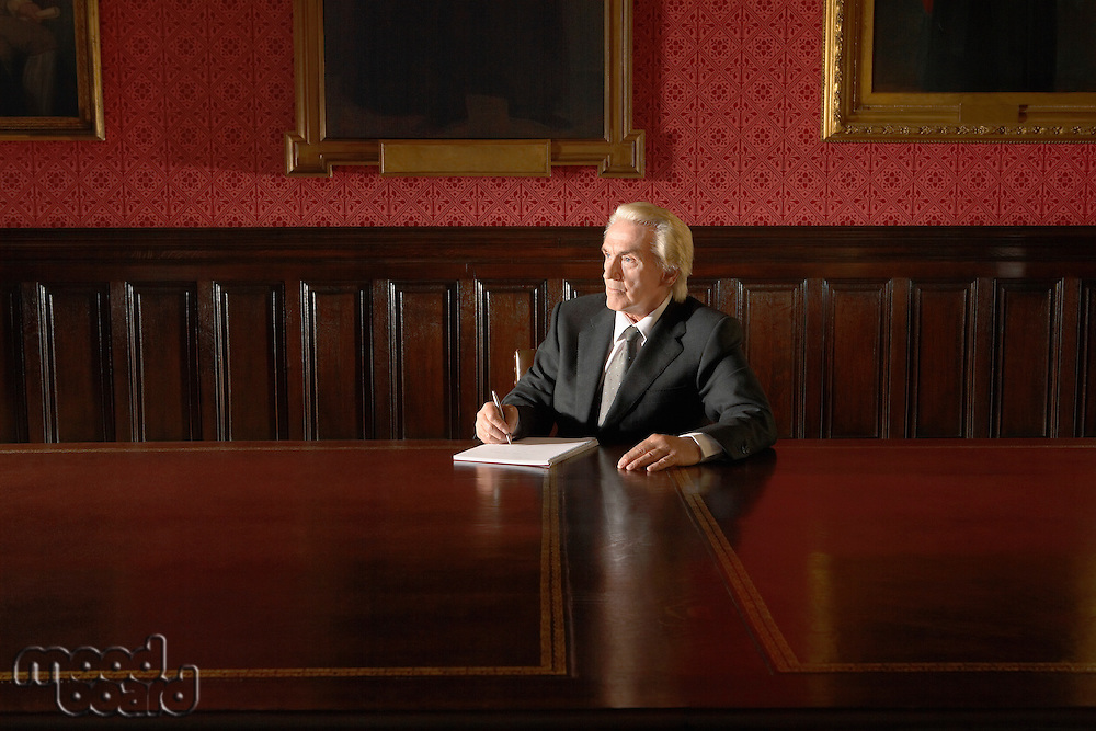 Man sitting in Board Room writing