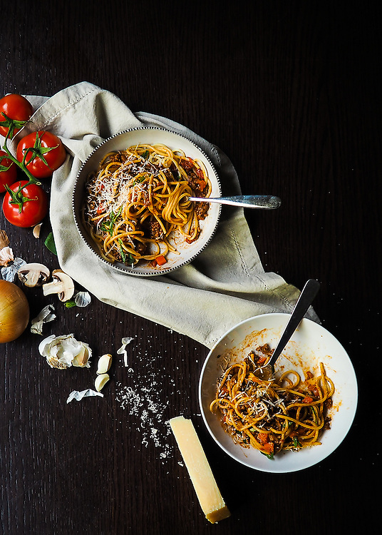 Spaghetti Bolognese dinner with shreds of parmesan cheese and ifresh ngredients