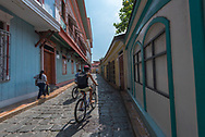 Guayaquil, Ecuador--April 15, 2018. Cyclists ride along a side street in the La Pensa, the bohemian artist enclave, in Guayaquil, Ecuador. Editorial use only.