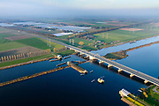 Nederland, Flevoland, Overijssel, Noordoostpolder, 04-11-2018. Ramspolbrug met N50, over de vaargeul het Ramsdiep. Naast de brug de balgstuw, onderdeel van Waterkering Kampen, tussen Ketelmeer en Zwarte Water (voorgeond). De balgstuw is een stormvloedkering en bestaat uit een opblaasbare dam of dijk, opgebouwd uit drie balgen. In niet-opgeblazen toestand liggen de balgen op de bodem. <br /> Ramspol bridge and Ramspol barrier, inflatable dike, between Ketelmeer and Black Water. The Balgstuw (bellow barrier) is a storm barrier and consists of an inflatable dam or dyke, composed of three bellows. Usually, each bellow rests on the bottom of the water.<br /> luchtfoto (toeslag op standaard tarieven);<br /> aerial photo (additional fee required);<br /> copyright© foto/photo Siebe Swart
