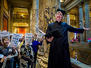 "04 MAY 2017 - ST. PAUL, MN: A Protestant minister reads bible passages supporting workers and women's rights in front of the Minnesota State Senate. About 200 people participated in a ""ISAIAH's 100 Days of Prophetic Resistance"" rally at the Minnesota State Capitol in St. Paul. They represented churches from across the Twin Cities and were demonstrating in favor of paid sick leave, child care, and a higher minimum wage. The Twin Cities are more liberal than rural Minnesota and many Twin Cities municipalities have passed ordinances with paid sick leave, child care and higher minimum wages. Republican legislators from rural Minnesota have tried to pass laws in the legislature rolling back those ordinances.     PHOTO BY JACK KURTZ"