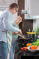 Happy couple preparing food in kitchen