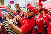 06 APRIL 2014 - BANGKOK, THAILAND: A woman dances with a hat decorated with photos of Thaksin Shinawatra, the exiled former Prime Minister of Thailand and Yingluck Shinawatra, the current Prime Minister and Thaksin's sister. Red Shirts and supporters of the government of Yingluck Shinawatra, the Prime Minister of Thailand, gathered in a suburb of Bangkok this weekend to show support for the government. The Thai government is dealing with ongoing protests led by anti-government activists. Legal challenges filed by critics of the government could bring the government down as soon as the end of April. The Red Shirt rally this weekend was to show support for the government, which public opinion polls show still has the support of most of the electorate.    PHOTO BY JACK KURTZ