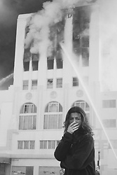 Woman crying in front of a burning building in California