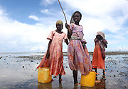 Three sisters collect shellfish in Fumba, Zanzibar.