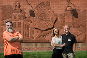 [From left] Artists, Tad Gallaugher, Tammy Spencer and Brad Spencer stand before the brick relief sculpture that they were commissioned to create as part of the Residential Housing Phase 1 project. The project, which included four new residence halls, the Living Learning Center and this sculpture were all celebrated during the opening ceremony and ribbon cutting event on Saturday, August 29, 2015 at the Living Learning Center on the Ohio University campus in Athens, Ohio.