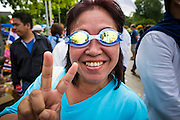 07 AUGUST 2013 - BANGKOK, THAILAND: A Thai anti-government Yellow Shirt wearing swim goggles in case police use tear gas, waves the V for Victory during a protest against a proposed amnesty bill. About 2,500 protestors opposed to an amnesty bill proposed by Thailand's ruling party marched towards the Thai parliament in the morning. The amnesty could allow exiled fugitive former Prime Minister Thaksin Shinawatra to return to Thailand. Thaksin's supporters are in favor of the bill but Thai Yellow Shirts and government opponents are against the bill. Thai police deployed about more than 10,000 riot police and closed roads around the parliament. Although protest leaders called off the protest rather than confront police, a few people were arrested for assaulting police when they tried to break through police lines. Several police officers left the scene under medical care after they collapsed in the heat.    PHOTO BY JACK KURTZ