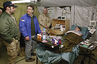 Al Franken, SMA Tilley, and Mark Wills visiting a sick soldier at K2 base in Uzbekistan, on USO Tour