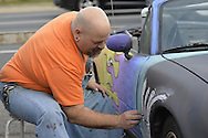 Bellmore, New York, USA. May 29, 2015. PHIL ZIRKULI, a Baldwin Art Teacher, is free-hand drawing colorful designs with chalk paint on his black 1992 Mazda Convertible at the Friday Night Car Show held at the Bellmore Long Island Railroad Station Parking Lot. Zirkuli explained he decorates his car to draw attention to the importance of art education. Hundreds of classic, antique, and custom cars are generally on view at the free weekly show, sponsored by the Chamber of Commerce of the Bellmores, from May to early October.
