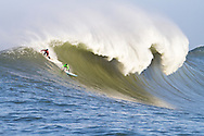 "Evan Slater (left) and Grant ""Twiggy"" Baker surf a giant wave during the first heat of the Mavericks surf contest Saturday, Feb. 13, 2010, in Half Moon Bay, California"
