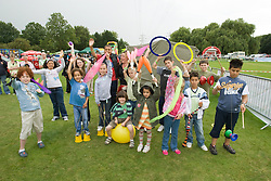 Group of children taking part in a Circus skills workshop waving at a Parklife summer activities event,