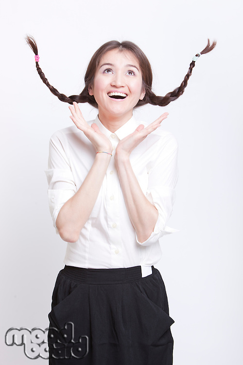 Cheerful young woman with braids curling upwards against white background