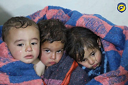 April 4, 2017 - AlHabeet, Idhib Province, Syria - Children victims from a result of shelling with chemical materials of the town of AlHabeet are wrapped in a blanket. Syrian Civil Defense aka the White Helmets, helped these young victims, after morning attack of a suspected serious lethal gas (most likely sarin nerve gas), in rebel-held Idlib Province in northwestern Syria, near Turkey (population 165,000). A score wounded and over dozen already dead, others might die shortly as a after effect of exposure to deadly gases. The inhabitants are overwhelmingly Sunni Muslims, although there is a significant Christian minority. (Credit Image: © Syria Civil Defense via ZUMA Wire)
