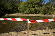 pole with red and white plastic warning tape
