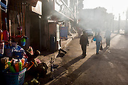 An Egytptian carrying a blue football walks through smoky air, emitted from a kebab business on a street in Luxor, Nile Valley, Egypt.