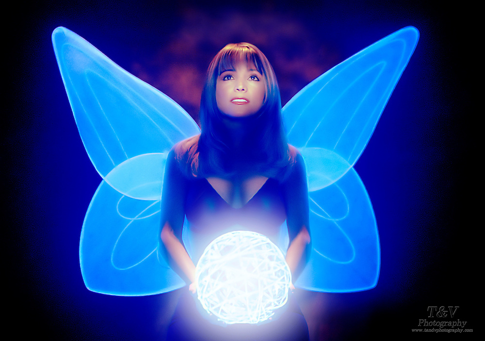 A young woman with wings holds a glowing twig ball.Black light