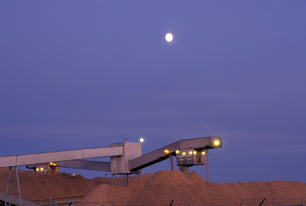 Canada, British Columbia, Full moon rises over piles of wood chips at Northwood Pulp Factory in city of Prince George