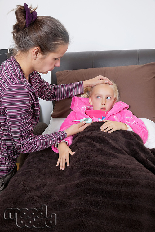 Mother checking unwell girl's temperature at home
