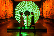 Candela by Felix de Pass, Montgomery and McIntyre supported by Officine Panerai - The trio have prepared an installation which glows in the Tapestry Gallery (the darkest place in the Museum). A disc treated with fluorescent paint, used on a clock face, responds to projected light which creates a sequence of patterns which slowly fade away. Candela is the term used for a measurement of light. The London Design Festival at the V&A, South Kensington, London 12 Sept 2014. Guy Bell, 07771 786236, guy@gbphotos.com