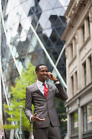 Happy businessman using cell phone outside building