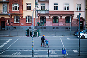 "Germany banned gatherings of more than 2 people called ""social distancing"" because of the coronavirus. A man and his child on roller scates crossing the street at the shore of river Main in Frankfurt which is very empty on a - normally very busy - Thursday evening."