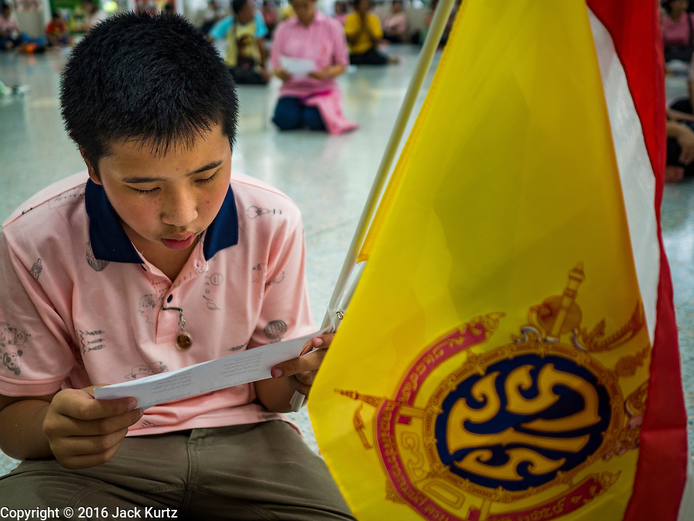 13 OCTOBER 2016 - BANGKOK, THAILAND:  A teenager, with the King's flag, prays for Bhumibol Adulyadej, the King of Thailand, at Siriraj Hospital Thursday morning before the King's death was announced. Thousands of people came to the hospital to pray for the beloved monarch. Bhumibol Adulyadej, the King of Thailand, died at Siriraj Hospital in Bangkok Wednesday, October 13, 2016. Bhumibol Adulyadej, 5 December 1927 – 13 October 2016, was the ninth monarch of Thailand from the Chakri Dynasty and is known as Rama IX. He became King on June 9, 1946 and served as King of Thailand for 70 years, 126 days. He was, at the time of his death, the world's longest-serving head of state and the longest-reigning monarch in Thai history.      PHOTO BY JACK KURTZ
