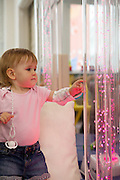 A young girl enjoys the bubble tower during a play therapy session.